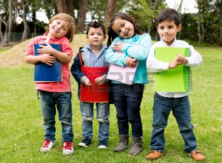 21788279-happy-group-of-school-kids-holding-notebooks-outdoors